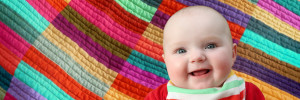 Laughing baby on a patchwork quilt